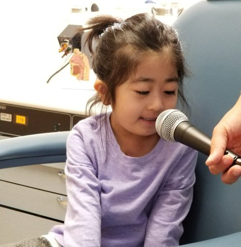 "Saying ""eeeeee"" as long as she can into the microphone"