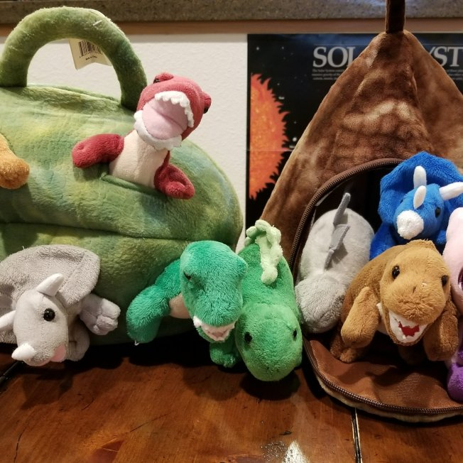 The stuffed dinosaurs are hatching out of egg and baby dinos are playing in volcano tent.