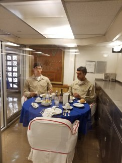 Wax figures of naval officers eating in a reserved area.